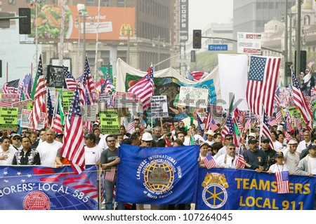 Union worker banners in front of immigrants participating in march for Immigrants and Mexicans protesting against Illegal Immigration reform by U.S. Congress, Los Angeles, CA, May 1, 2006 - stock photo