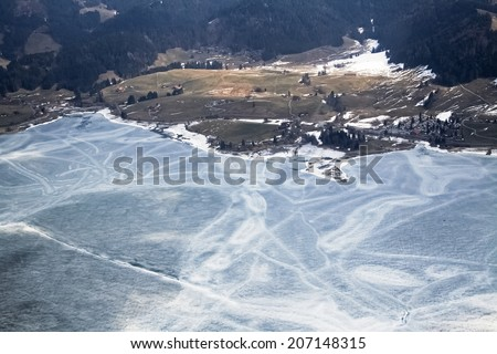 Unique and magnificent airplane aerial view of central snow-capped Swiss Alps, lakes, and blue skies patched with dramatic high cloud formations. - stock photo