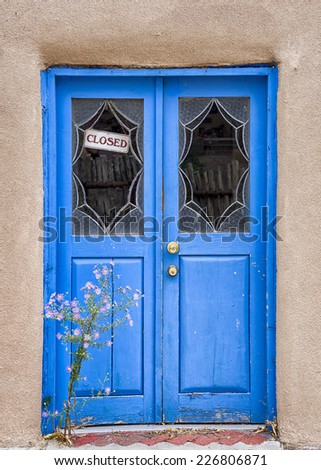 Unique blue door fronted by purple aster flowers in Santa Fe, NM - stock photo