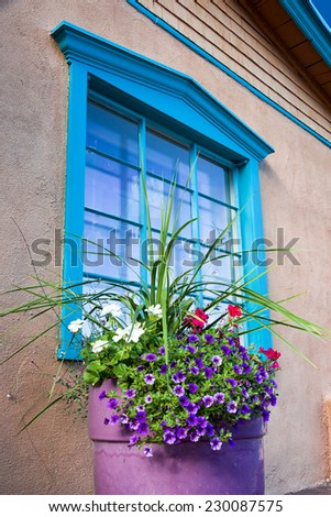 Unique blue window fronted by multicolored flowers in Santa Fe, NM - stock photo