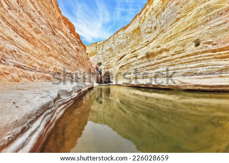 Unique canyon in Israel - En Avdat. Striped sandstone walls and cold stream. In the water reflected the canyon walls and sky - stock photo