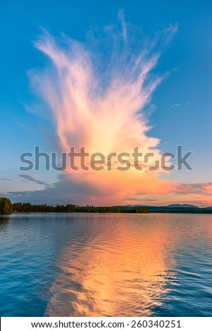 unique cloud formation reflecting in a calm lake in northern Sweden - stock photo