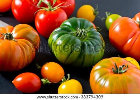 unique colorful ripe tomatoes on black background. - stock photo