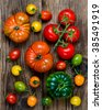 unique colorful ripe tomatoes on wooden background. - stock photo