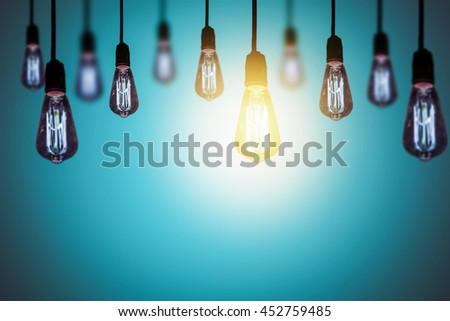 Unique concept, row of light bulb with growing one - stock photo