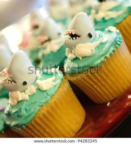 Unique cupcakes with sharks and green frosting with white. - stock photo