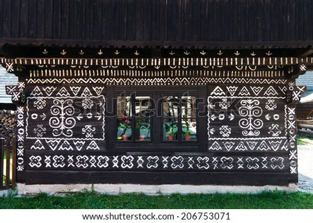 Unique decoration of log houses based on patterns used in traditional embroidery in village of Cicmany, UNESCO World Heritage Site, Slovakia - stock photo