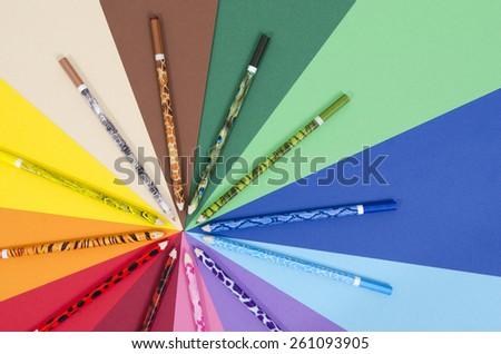 Unique design color pencils on paper. All colors pencils arranged in a circle on rainbow color paper. - stock photo