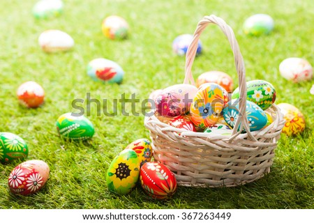 Unique hand painted Easter eggs in basket on grass. Traditional decoration in sun light - stock photo