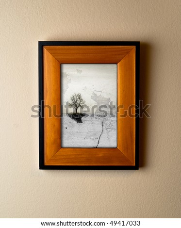 Unique lone tree art work in a beautiful wooden frame. Interior decor element with original artwork. - stock photo