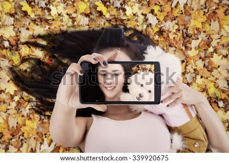 Unique perspective of beautiful woman using smartphone to take selfie photo with her dog on the autumn leaves - stock photo