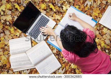 Unique perspective of college student lying on the autumn leaves at park while studying with laptop and books - stock photo