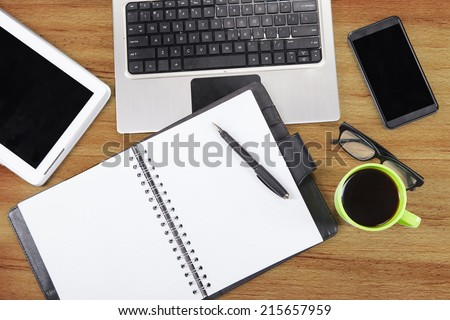 Unique Perspectives of a business table with an agenda, digital tablet, laptop, smart phone, glasses, and coffee - stock photo