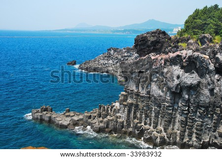 Unique rock formation with volcano in background - stock photo