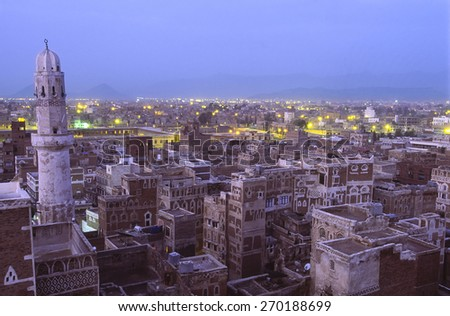 Unique view of the rooftops of Sana, capital city of Yemen, in evening at blue hour with mosque in foreground - stock photo