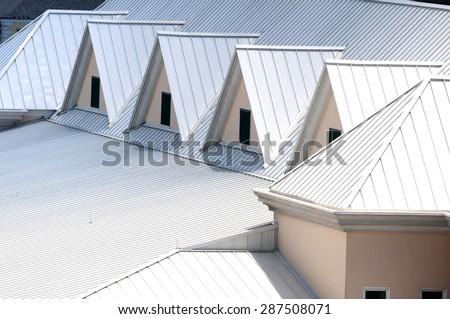 Unique white triangular shaped aluminum metal roof designed for maximum rain repulsion and heat reflection - stock photo