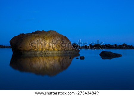 Uniquely lit, dramatic rock formation in a tranquil sea, reflecting on the surface of deep blue colored water. Calmness, tranquility, meditation, calm before the storm concept, blue background. - stock photo