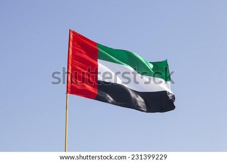 United Arab Emirates flag flying in the blue sky - stock photo