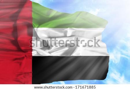 United Arab Emirates waving flag against blue sky with sunrays - stock photo