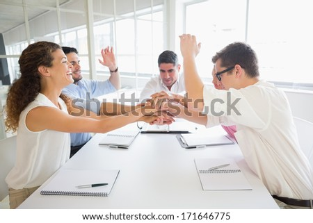 United business people stacking hands at conference table in office