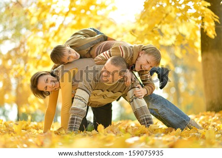 united family on a walk during the fall of the leaves in the park - stock photo