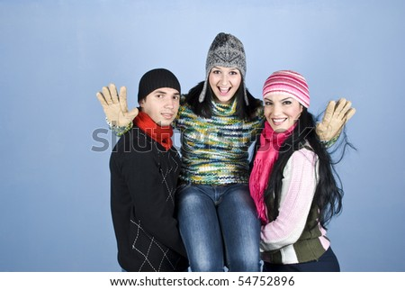 United friends laughing and having fun over blue background,two of them holding on arms a woman up