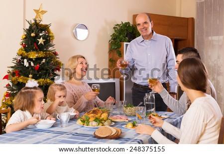 United happy family at festive table near Christmas tree - stock photo