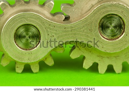 United joint machinery element of two cylindrical cogwheel fragments spinning together as system of connected parts, symbolizing thinking concept and mechanical approach to kinetic theoretic problems - stock photo
