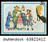 UNITED KINGDOM - CIRCA 1978: A British Used Christmas Postage Stamp showing Carol Singers, circa 1978 - stock photo