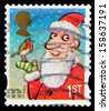 UNITED KINGDOM - CIRCA 2012: A British Used Christmas Postage Stamp showing Father Christmas and Robin, circa 2012  - stock photo