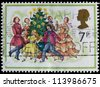 UNITED KINGDOM - CIRCA 1977: A post stamp printed in the Great Britain shows Carol Singers around a Christmas Tree, circa 1977 - stock photo