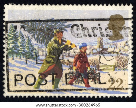 UNITED KINGDOM - CIRCA 1990: A stamp printed in the United Kingdom shows Man Carry Christmas Tree, circa 1990. - stock photo