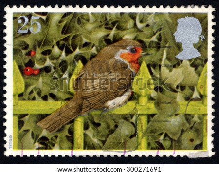 UNITED KINGDOM - CIRCA 1995: A stamp printed in the United Kingdom shows the European Robin on Railings and Holly, circa 1995.  - stock photo