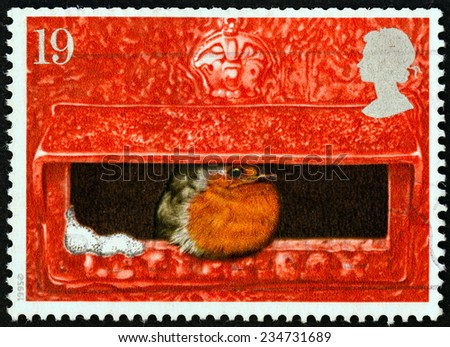 """UNITED KINGDOM - CIRCA 1995: A stamp printed in United Kingdom from the """"Christmas """" issue shows European Robin in Mouth of Pillar Box, circa 1995.  - stock photo"""