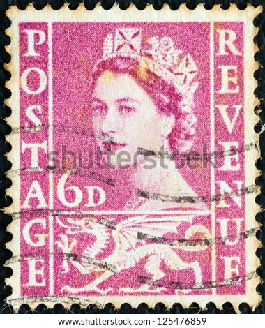 UNITED KINGDOM - CIRCA 1958: A stamp printed in Wales shows a portrait of Queen Elizabeth II and Welsh Dragon symbol, circa 1958. - stock photo