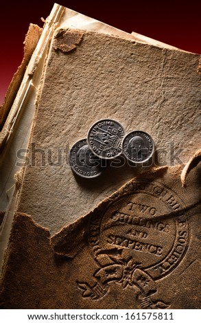 United Kingdom pre-decimal 1971 currency. Pounds, shillings and pence on old damaged bible book stamped with the  price, two shillings and six pence. - stock photo
