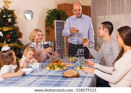 United smiling family at festive table near Christmas tree