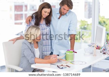 United smiling team of interior designer at desk in bright modern office - stock photo