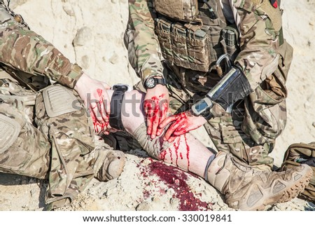 United States Army ranger medic treating the wounds of his injured fellow in arms in the mountains - stock photo