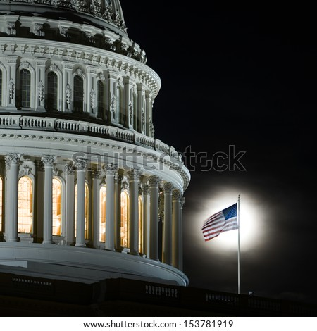 United States Capitol Building dome detail with flapping National Flag on full moon background at night