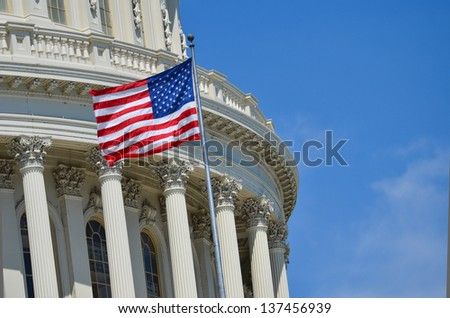 United States Capitol Building dome detail with flapping US flag - Washington DC - stock photo