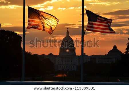 United States Capitol building silhouette and US flags at sunrise - Washington DC - stock photo