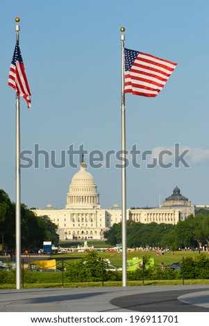 United States Capitol building with US flags around Washington Monument - Washington DC  - stock photo