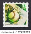 UNITED STATES - CIRCA 2000: A postage stamp printed in USA showing an image of a baseball ball breaking a newspaper about the new baseball records, circa 2000. - stock photo