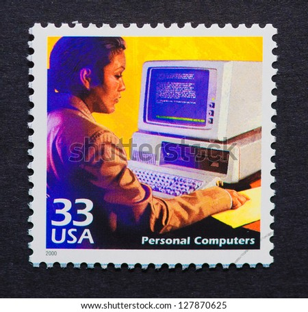 UNITED STATES - CIRCA 2000: a postage stamp printed in USA showing an image of a woman using an old computer, circa 2000. - stock photo