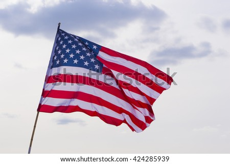 United States Flag at Background of Sky - stock photo