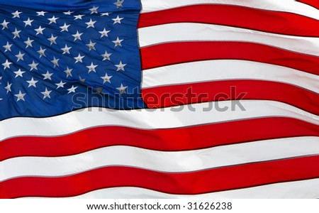 United states flag blowing in a stiff breeze, filling the frame,