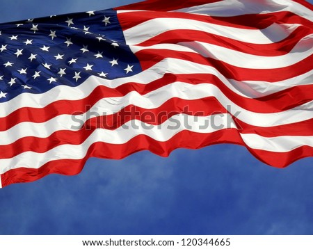 United States flag blows in the wind against a blue sky - stock photo