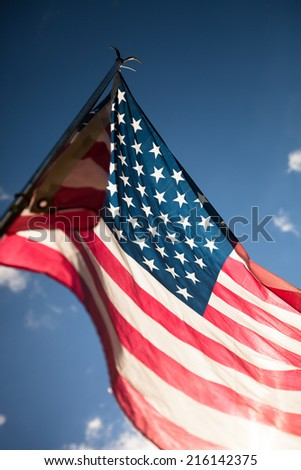 United States flag blows in the wind against a blue sky on a sunny day - stock photo