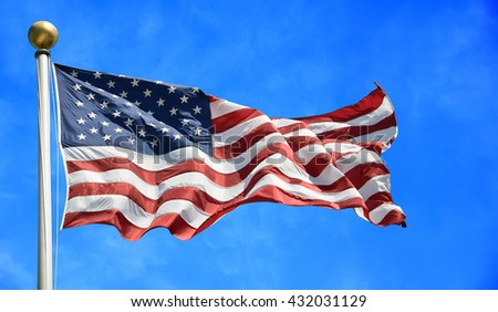 United States flag blows in the wind against blue sky - stock photo